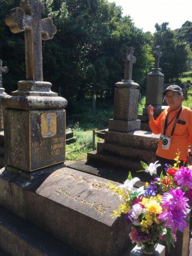 マルマン神父のお墓の前で語るツアーガイドの大村さん